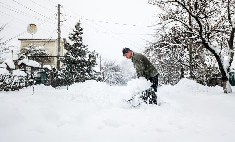 L'uomo con una pala libera la pista dalla neve fotografia stock libera da diritti