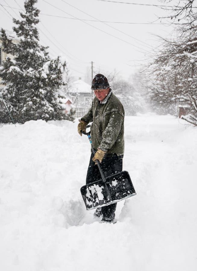 L'uomo con una pala libera la pista dalla neve immagini stock libere da diritti
