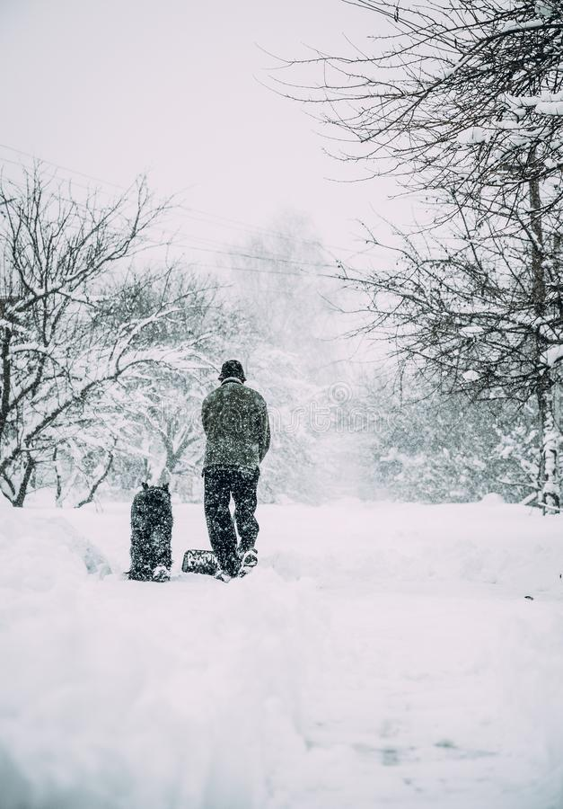 L'uomo con una pala libera la pista dalla neve immagine stock