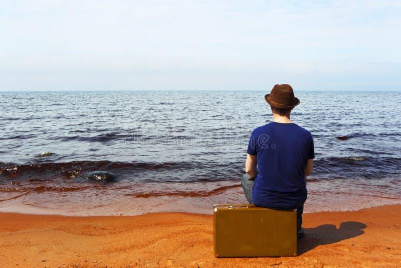 L'uomo con una valigia su una spiaggia fotografie stock