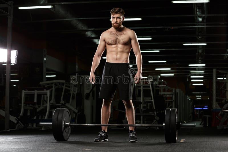 L'uomo concentrato di sport fa gli esercizi di sport con il bilanciere fotografia stock libera da diritti