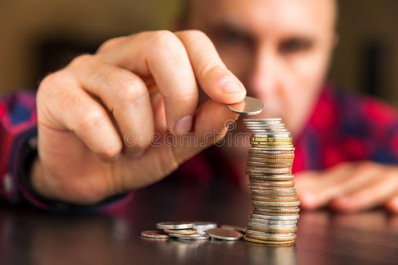 L'uomo conta le sue monete su una tavola fotografia stock