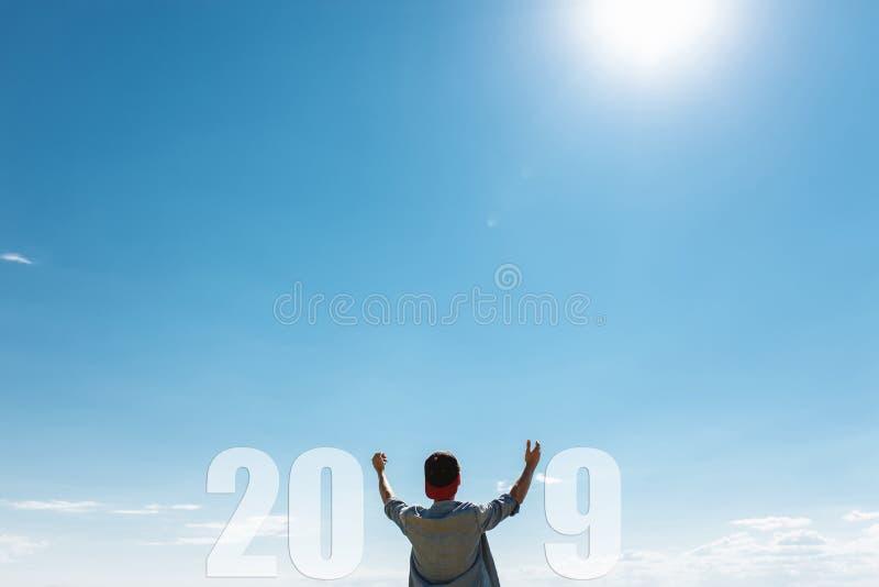 L'uomo, contro il cielo blu, il tipo tira le mani verso il cielo, il concetto di nuovo 2019 anni fotografie stock libere da diritti
