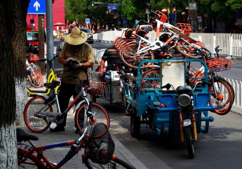 L'uomo controlla i bicyles locativi nelle vie di Pechino, Cina fotografia stock