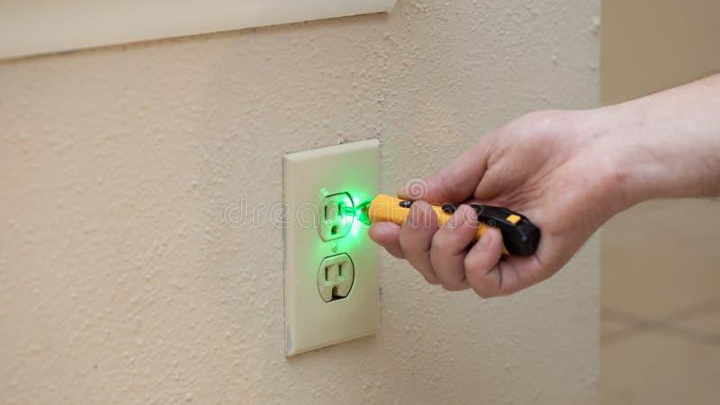 L'uomo controlla se c'è potere in presa a muro con lo strumento immagini stock