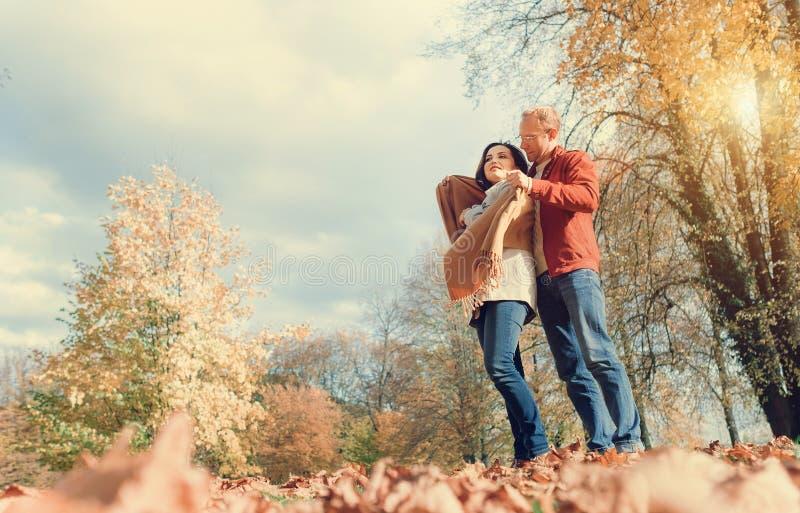 L'uomo copre le sue spalle della moglie di scialle caldo nel parco di autunno fotografie stock