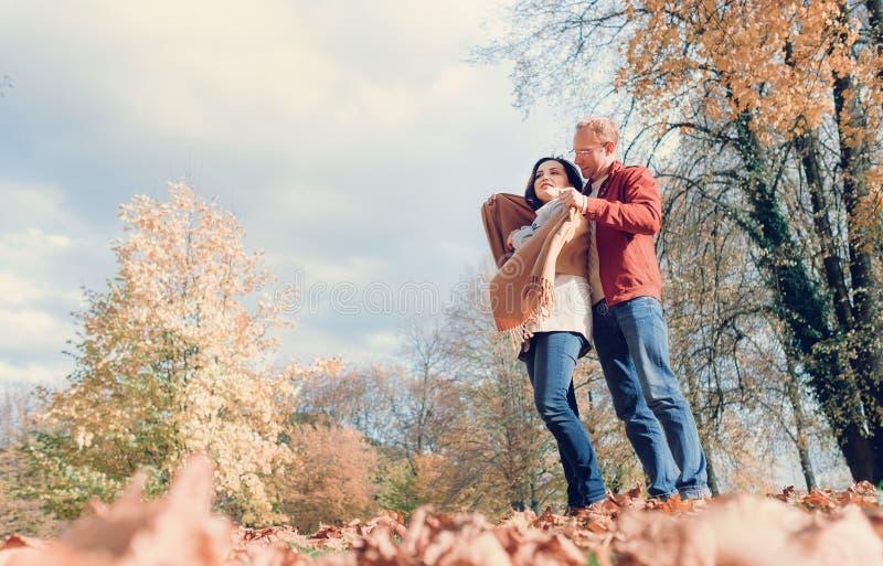 L'uomo copre le sue spalle della moglie di scialle caldo nel parco di autunno fotografia stock libera da diritti