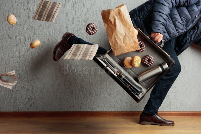 L'uomo corre in ufficio: è in ritardo e perde il contenuto della sua valigetta fotografia stock