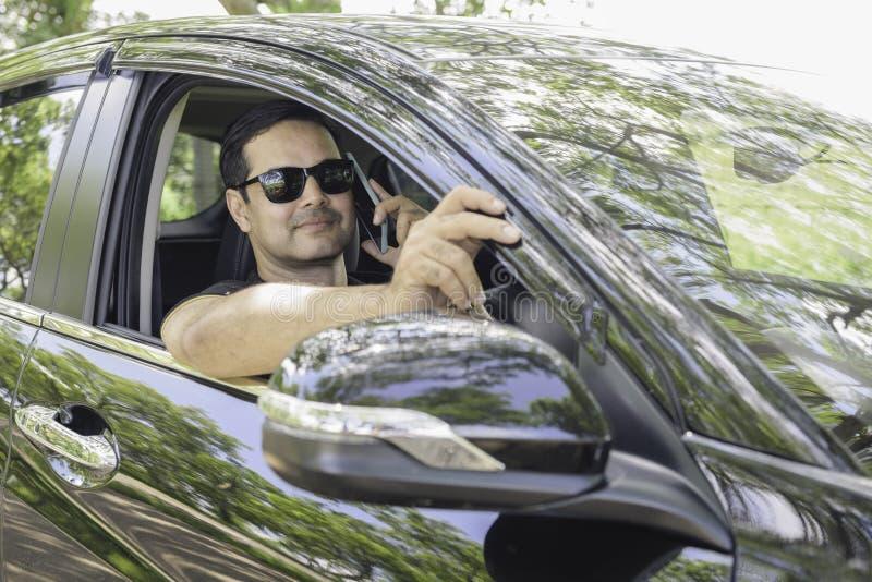 L'uomo cuasual asiatico di affari si siede nello sguardo dell'automobile alla macchina fotografica ed usa la calca immagine stock