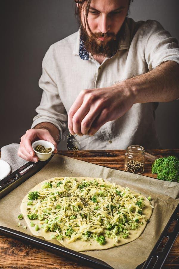 L'uomo cucina la pizza con i broccoli e la salsa di pesto fotografia stock