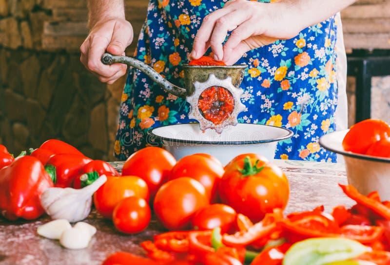 L'uomo cucina la salsa casalinga, pezzi di frantumazioni del ketchup dei pomodori maturi in una tritacarne d'annata anziana della immagine stock