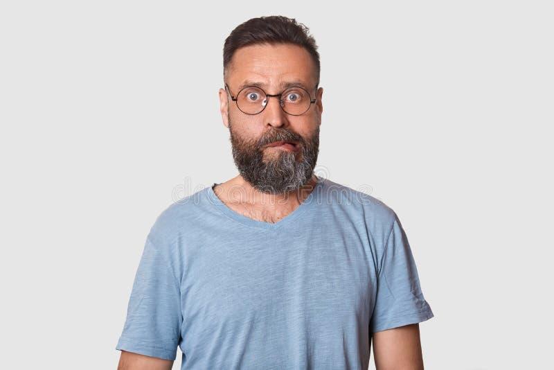L'uomo curioso invecchiato medio impressionato con la barba nera ha espressione facciale sconosciuta con la sensibilità della rep immagini stock libere da diritti