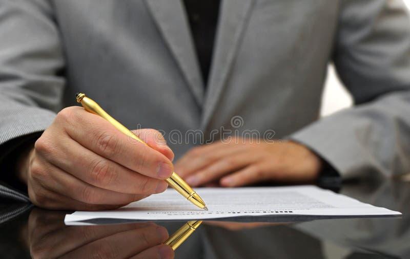 L'uomo d'affari è contratto soddisfacente e di firma fotografia stock libera da diritti