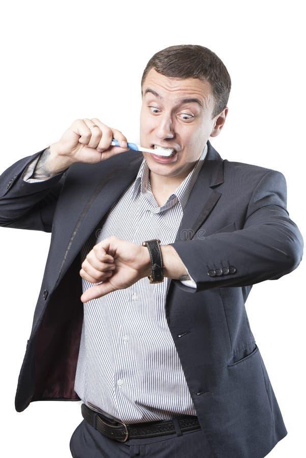 L'uomo d'affari è in ritardo Pulisce i suoi denti ed esamina il suo orologio nel panico immagini stock libere da diritti