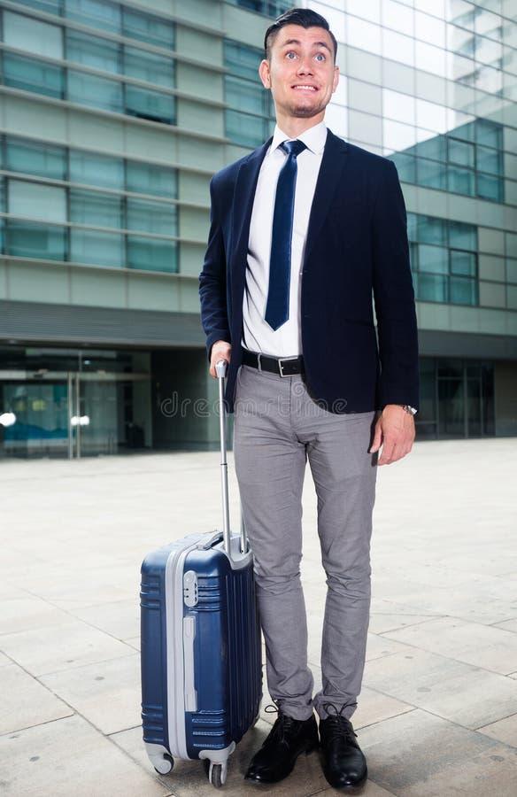L'uomo d'affari adulto in vestito con la valigia sta restando immagini stock libere da diritti