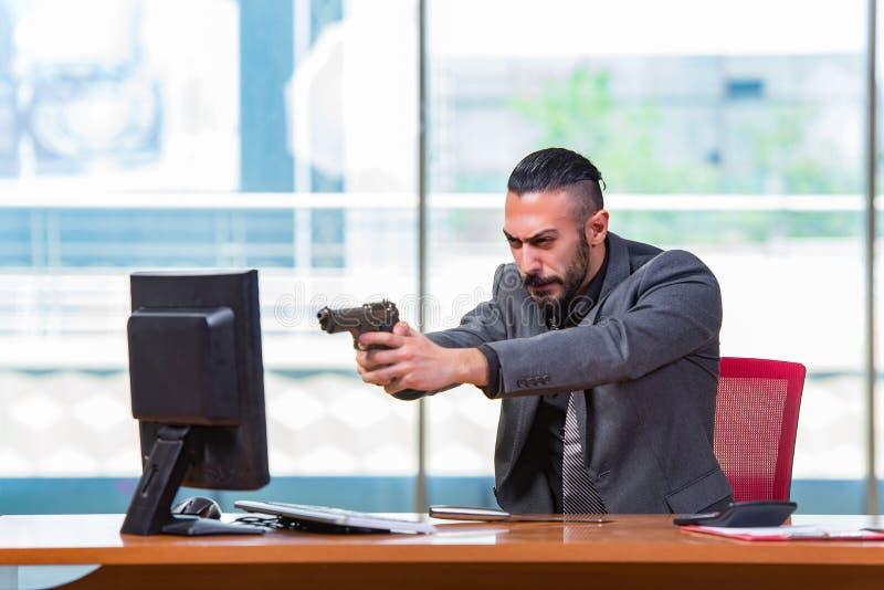 L'uomo d'affari aggressivo arrabbiato con la pistola nell'ufficio fotografie stock