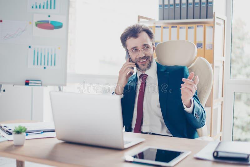 L'uomo d'affari allegro sta avendo una conversazione telefonica sul lavoro Lui immagine stock