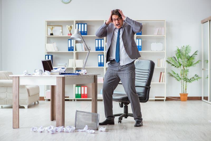 L'uomo d'affari arrabbiato ha colpito il lavoro nell'ufficio infornato licenziato immagini stock libere da diritti