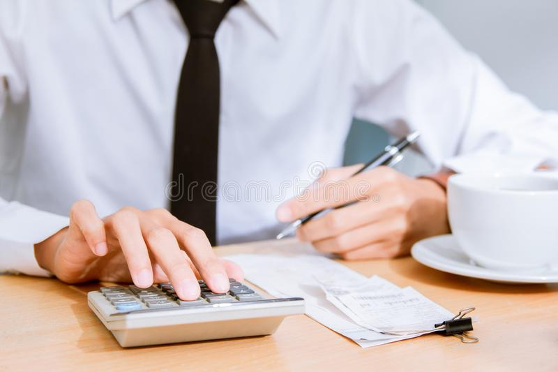 L'uomo d'affari asiatico in camicia e smoking bianchi, calcola la tassa che conduce alla liquidazione di stabilimento fotografie stock libere da diritti