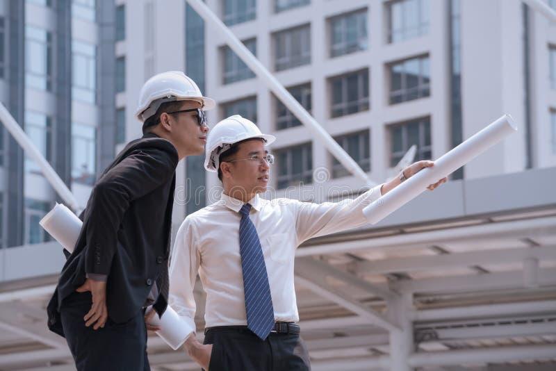 L'uomo d'affari asiatico discute con l'architetto w professionale dell'ingegnere fotografie stock