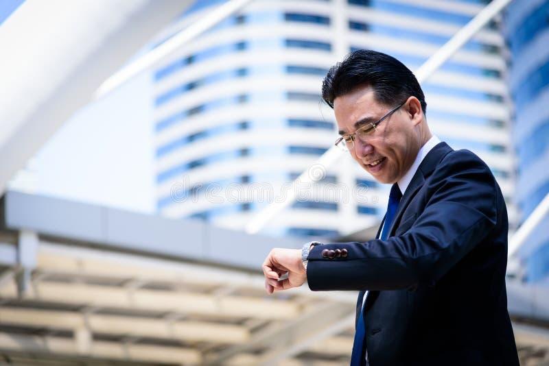 L'uomo d'affari asiatico ha la tenuta della borsa nera e considerare l'orologio nella fretta del tempo immagini stock