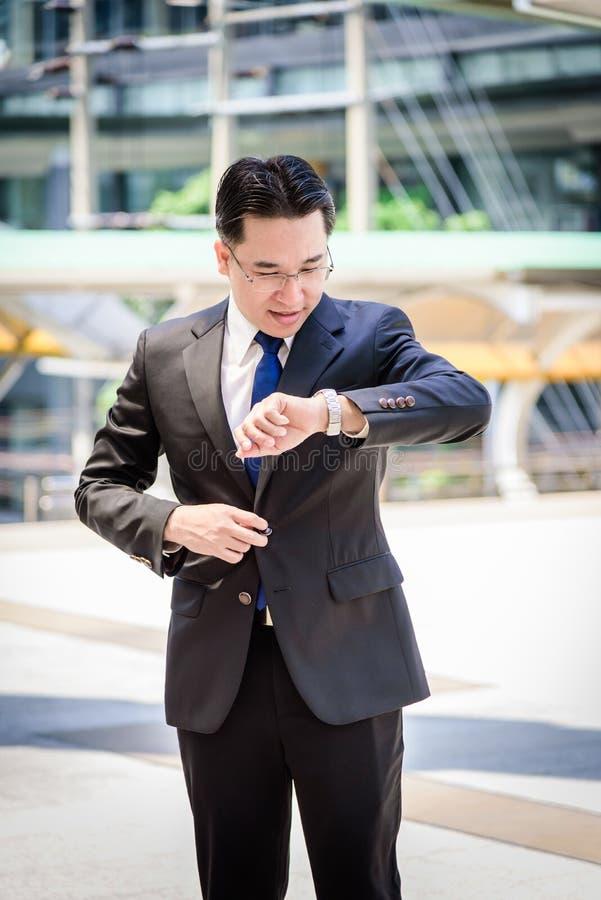 L'uomo d'affari asiatico ha la tenuta della borsa nera e considerare l'orologio nella fretta del tempo fotografia stock libera da diritti