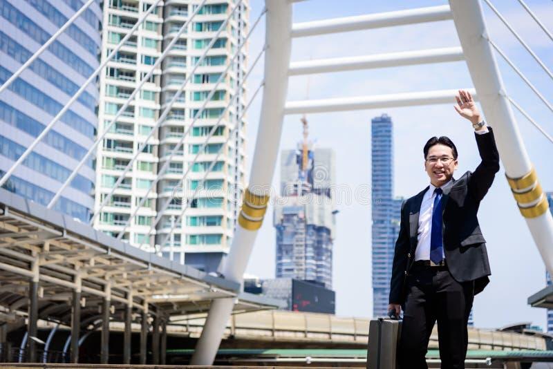 L'uomo d'affari asiatico ha la tenuta della borsa nera e fabbricazione del ciao g immagine stock libera da diritti