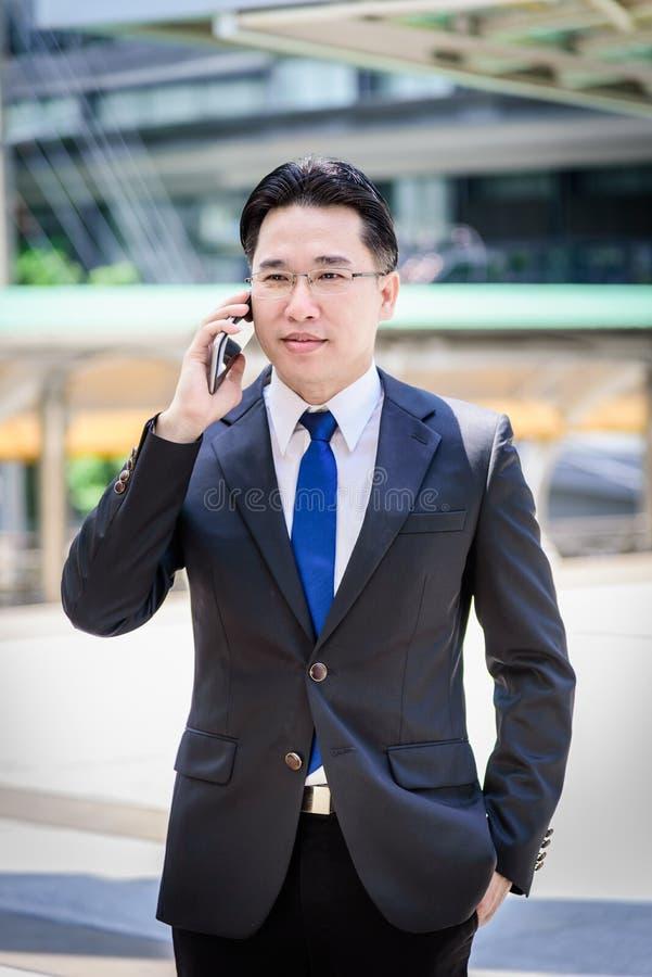 L'uomo d'affari asiatico ha lavorare al cellulare con felice fotografia stock