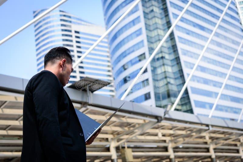 L'uomo d'affari asiatico ha tenuta una cartella documenti e delle sedere nere fotografie stock