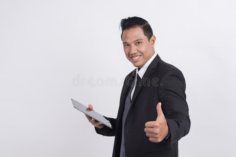 L'uomo d'affari asiatico sorridente felice con i pollici aumenta il gesto che esamina la macchina fotografica immagini stock libere da diritti