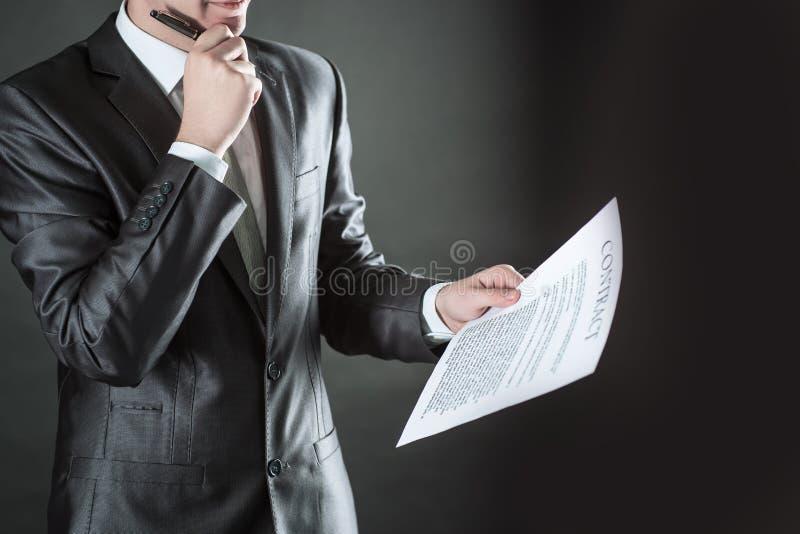L'uomo d'affari attento sta considerando i termini di nuovo contratto fotografia stock libera da diritti