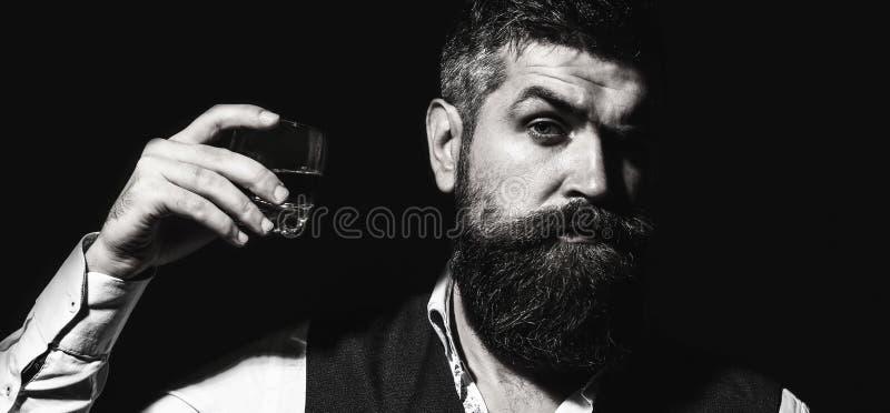 L'uomo d'affari barbuto dentro sta tenendo un vetro di whiskey Uomo ben vestito bello in rivestimento con vetro della bevanda adu immagine stock