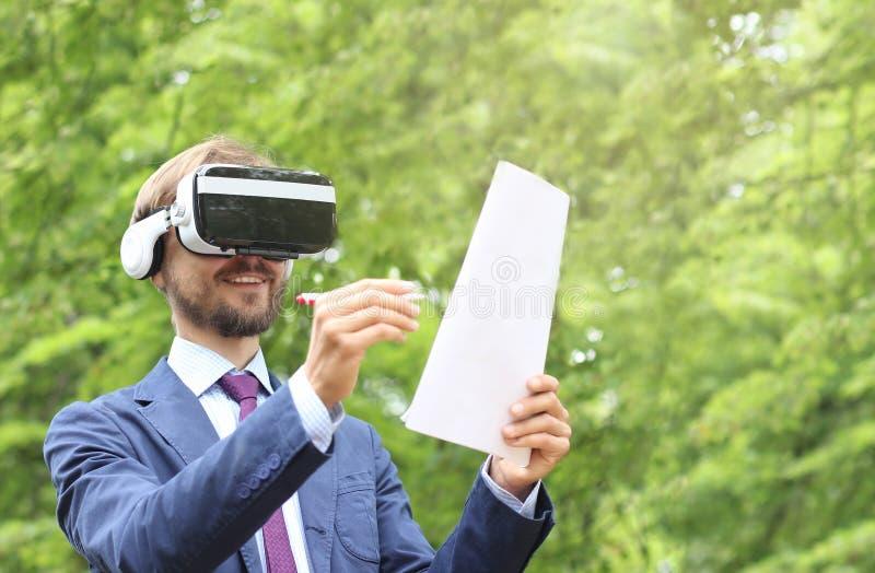 L'uomo d'affari barbuto felice con i vetri di realtà virtuale firma il documento fotografia stock