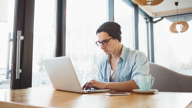 L'uomo d'affari bello in abbigliamento casual ed occhiali sta utilizzando un computer portatile in caffè fotografie stock