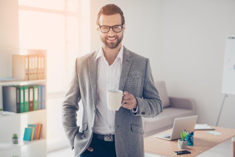 L'uomo d'affari bello felice in camicia e rivestimento bianchi tiene la tazza o fotografie stock libere da diritti