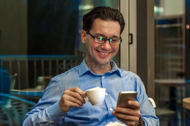 L'uomo d'affari bello in occhiali sta utilizzando uno smartphone, sta tenendo una tazza di caffè e sta sorridendo mentre stava vi fotografia stock