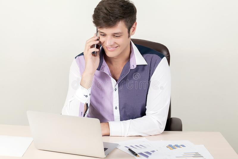 L'uomo d'affari bello sta rivolgendo al suo telefono cellulare all'ufficio immagini stock