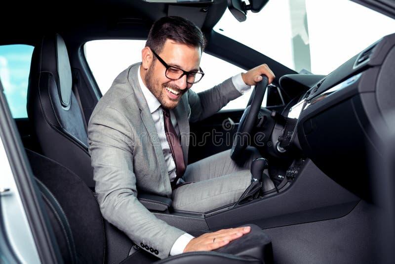 L'uomo d'affari bello sta sedendosi in una nuova automobile nel concessionario auto immagini stock libere da diritti