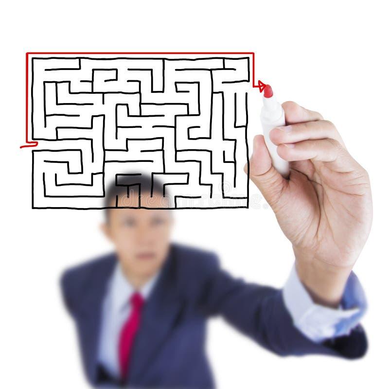 L'uomo d'affari cercano e l'uscita di scrittura dal problema del labirinto fotografie stock
