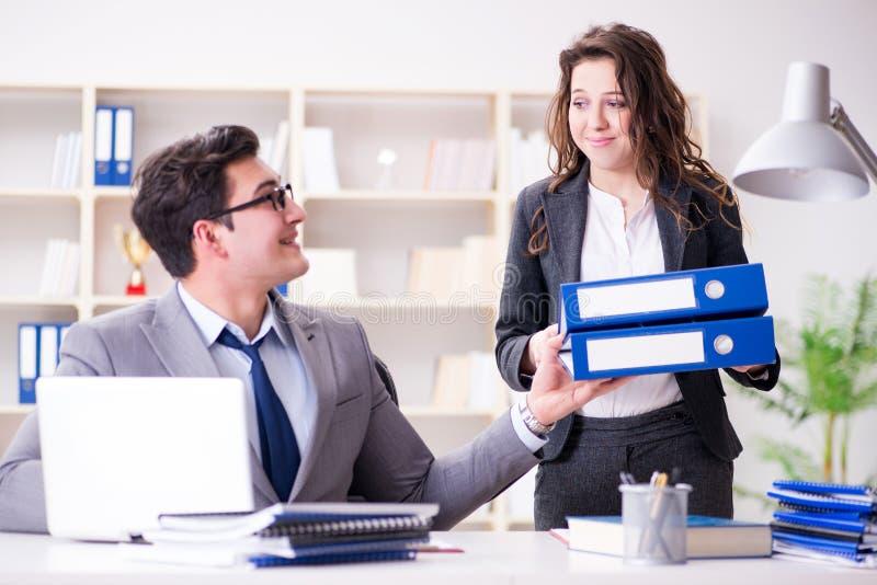 L'uomo d'affari che chiede il lavoro di ufficio dal suo segretario di aiuto immagini stock