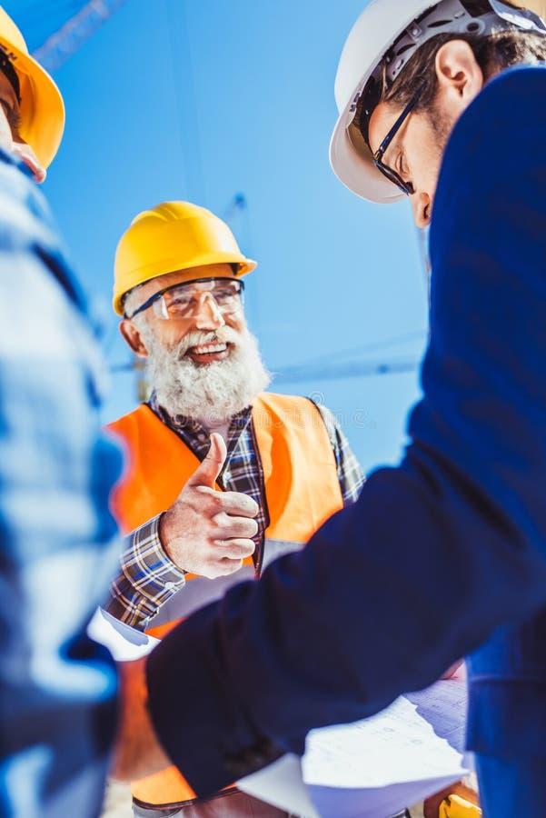 L'uomo d'affari che esamina la costruzione progetta mentre un muratore sta mostrando immagini stock