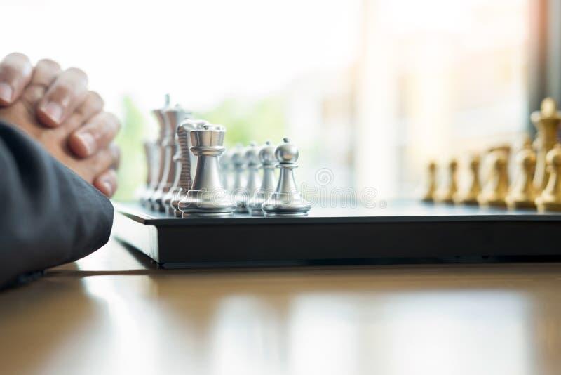 l'uomo d'affari che gioca il gioco di scacchi dipende la tavola di legno per il nuovo piano di strategia dell'analisi, il capo de immagini stock libere da diritti