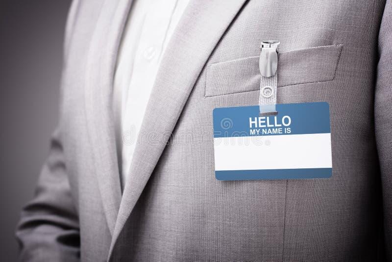 L'uomo d'affari che indossa il ciao il mio nome è etichetta fotografia stock