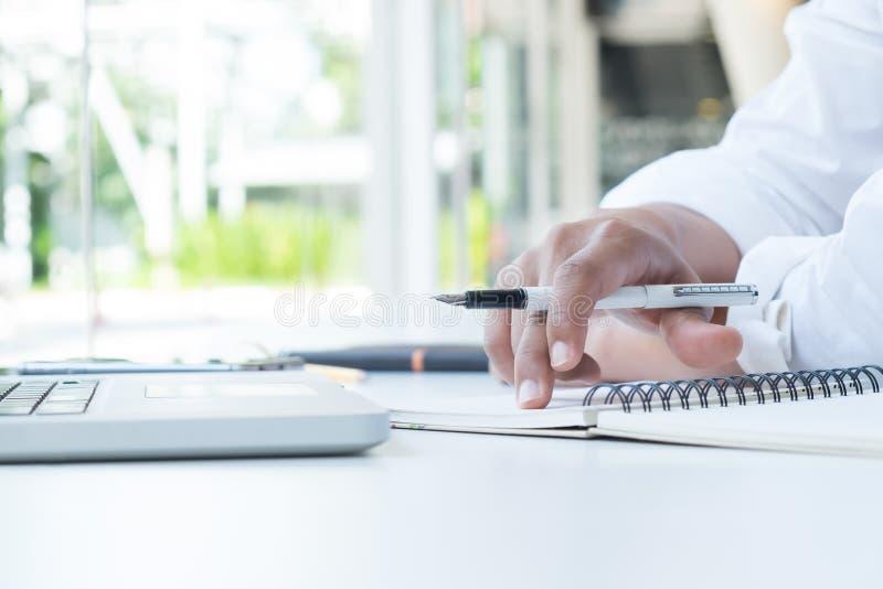 L'uomo d'affari che lavora nell'ufficio analizza i dati di vendita di affari immagini stock