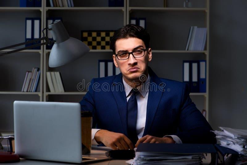 L'uomo d'affari che lavora tardi alla notte in ufficio per l'indennità di ore straordinarie fotografia stock