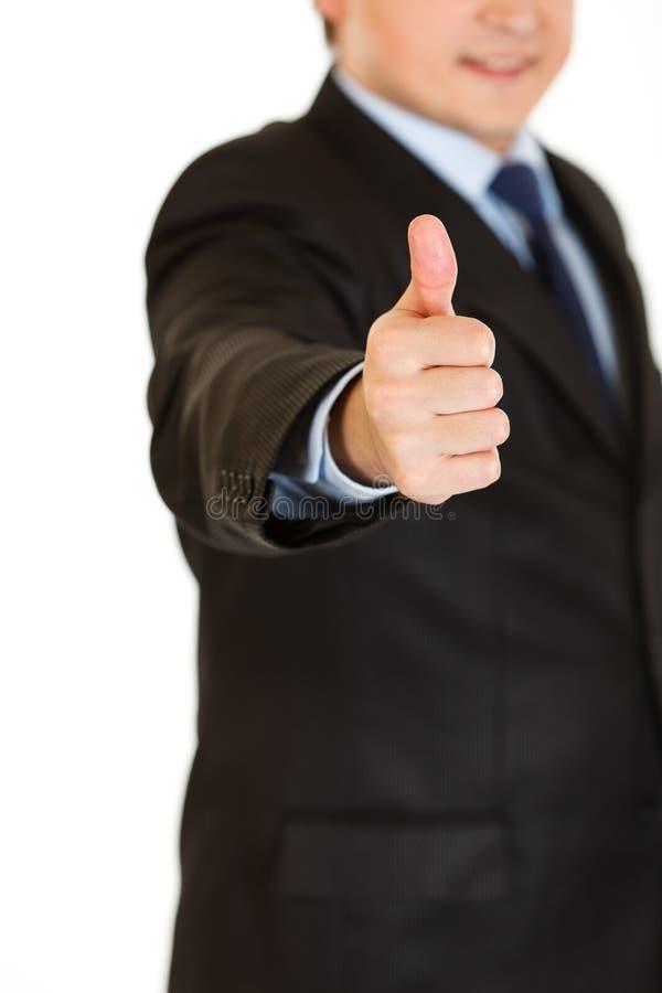 L'uomo d'affari che mostra i pollici aumenta il gesto. Primo piano. fotografia stock