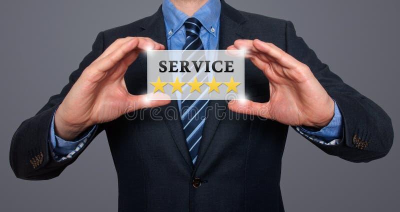 L'uomo d'affari che tiene la carta bianca con le stelle di servizio cinque firma, Gre immagine stock libera da diritti