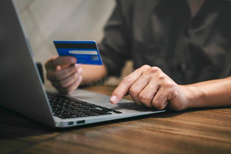L'uomo d'affari che tiene la carta di credito e che scrive sul computer portatile per acquisto ed il pagamento online fa un acqui immagini stock libere da diritti