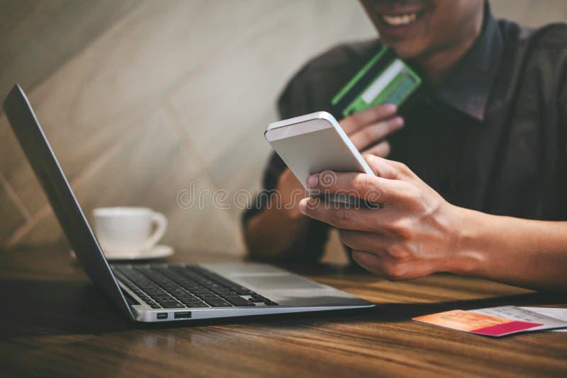 L'uomo d'affari che tiene la carta di credito e che scrive sul computer portatile per acquisto ed il pagamento online fa un acqui fotografia stock libera da diritti