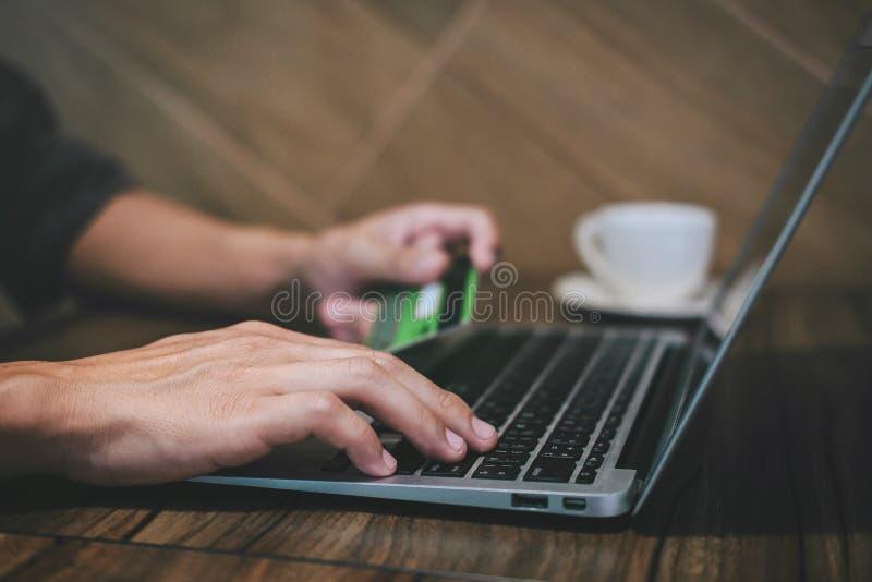 L'uomo d'affari che tiene la carta di credito e che scrive sul computer portatile per acquisto ed il pagamento online fa un acqui immagine stock libera da diritti